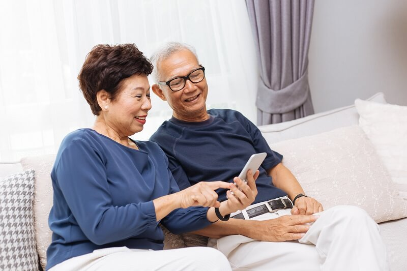 elderly asian couple on phone