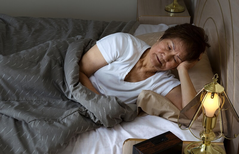 Senior woman lying in bed awake